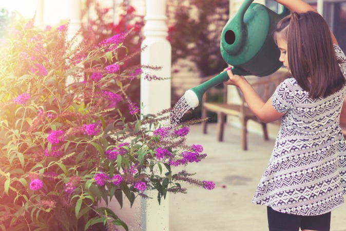 Canva - Girl Watering Flowers