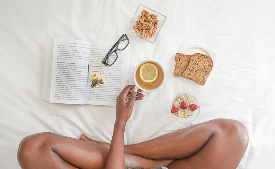 Canva - Person Holding White Ceramic Mug With Lemon Near Book and Sliced Bread on White Comforter